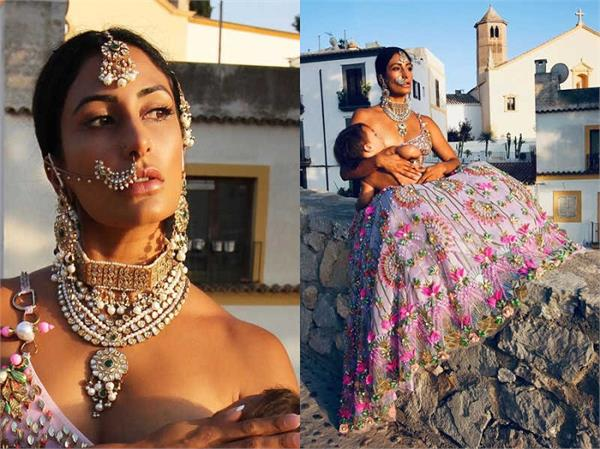 south asian woman breastfeeding her son wearing a lehenga is the picture